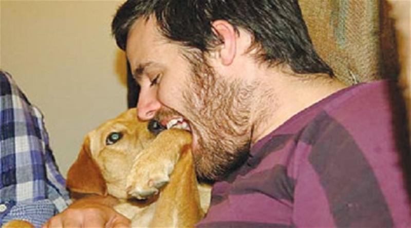 رجل يعض أنف كلب