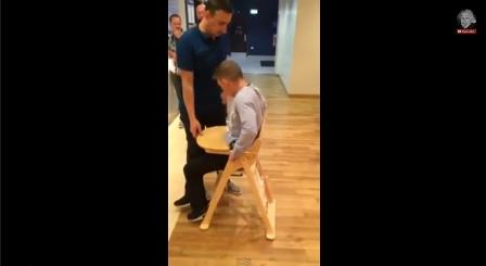 رجل يعلق في كرسي مخصص للرضع