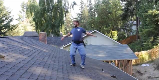 عامل بناء يستمتع بوقته أثناء إصلاح سقف أحد المنازل