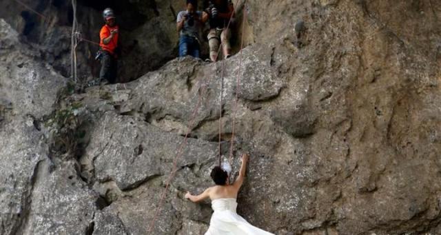 زوجان يتسلقان جبلا لالتقاط أخطر صور زفاف فى العالم