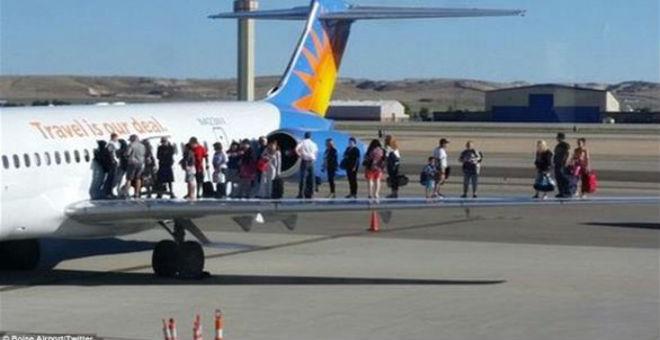 ركاب يهربون من دخان الطائرة بالوقوف على جناحها