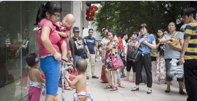 بالصور.. أم صينية يائسة تمنح أطفالها للغرباء مجانا