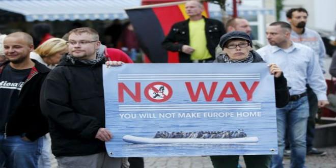 أنصار اليمين المتطرف في ألمانيا يحملون لافتة ضد اللاجئين