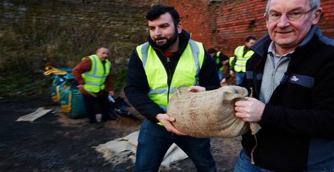 بريطانيا: اللاجئون السوريون يتطوعون للمساعدة لمواجهة آثار الفيضانات