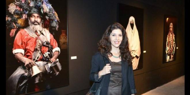 المصورة المغربية ليلى العلوي بجانب صور  لمعرض لها في لبنان