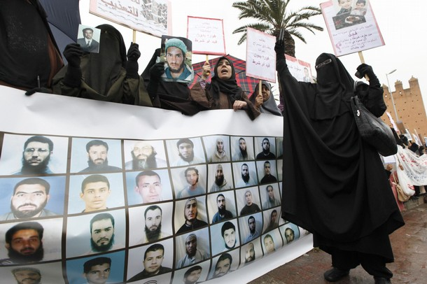 Veiled women hold signs during a protest demanding broad political reforms in Rabat