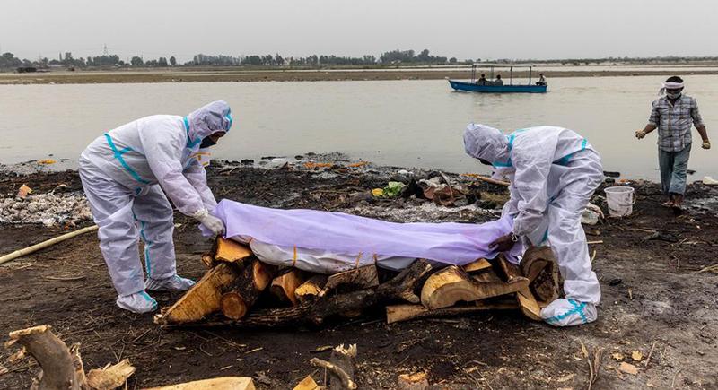 هنود يتخلصون من جثث ضحايا كورونا في الانهار